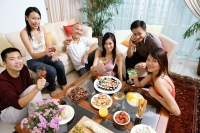 Adults sitting in living room, having a party, smiling at camera - Alex Microstock02