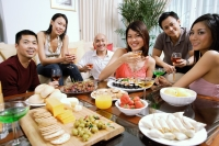 Adults having a party in living room, smiling at camera, food on coffee table - Alex Microstock02