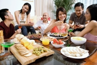 Adults having a party in living room, food on coffee table - Alex Microstock02
