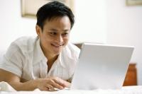 Man in bedroom, using laptop - Alex Microstock02