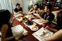 Adults sitting around dinner table, woman taking from plate being passed around - Alex Microstock02