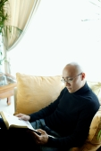 Man in black turtleneck, sitting on sofa in living room, reading book - Alex Microstock02