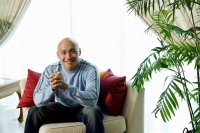 Man sitting on sofa in living room, smiling at camera - Alex Microstock02