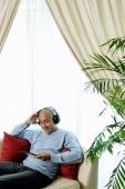 Man on sofa with headphones, listening to music - Alex Microstock02