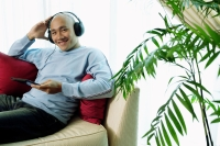 Man on sofa with headphones, listening to music, smiling at camera - Alex Microstock02