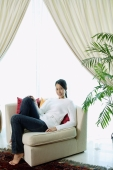 Woman in living room, sitting on sofa, smiling at camera - Alex Microstock02