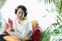 Woman sitting on sofa, wearing headphones, holding CD case, smiling - Alex Microstock02