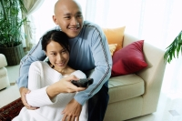 Couple in living room, woman holding remote control - Alex Microstock02