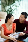 Couple at home, photo album in front of them - Alex Microstock02