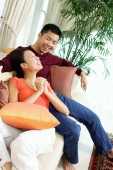 Couple in living room, sitting on sofa, woman with hands clasped - Alex Microstock02