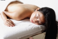 Woman lying on massage table, eyes closed - Alex Microstock02