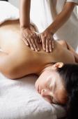 Woman lying on massage table, having back massaged - Alex Microstock02