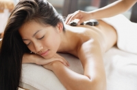 Woman having stones placed on her back as massage treatment - Alex Microstock02