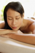 Woman lying on massage table, leaning head on arms, eyes closed - Alex Mares-Manton