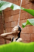 Woman taking outdoor shower, eyes closed - Alex Mares-Manton