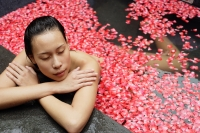 Woman leaning at edge of tub, flowers floating in water - Alex Mares-Manton