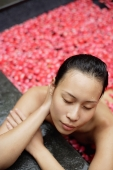 Woman leaning on edge of tub filled with floating rose petals, eyes closed - Alex Mares-Manton