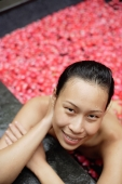 Woman leaning on edge of tub filled with floating rose petals, smiling at camera - Alex Mares-Manton