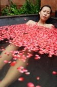 Woman in tub filled with floating rose petals - Alex Mares-Manton