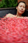 Woman in tub filled with floating rose petals, eyes closed - Alex Mares-Manton