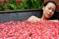 Woman in tub with floating rose petals, eyes closed - Alex Mares-Manton