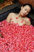 Woman relaxing in tub with floating rose petals, eyes closed - Alex Mares-Manton