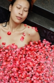 Woman with eyes closed, relaxing in tub with floating rose petals - Alex Mares-Manton
