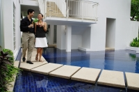 Couple walking next to swimming pool, champagne glasses in hand - Alex Mares-Manton