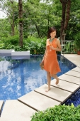 Woman walking by swimming pool, holding glass of champagne and carrying sandals - Alex Mares-Manton