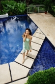 Woman in green dress walking across swimming pool, smiling at camera - Alex Mares-Manton
