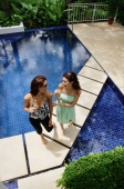 Two women standing next to swimming pool, talking - Alex Mares-Manton
