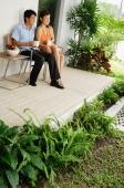 Couple sitting on patio having coffee, looking away - Alex Mares-Manton