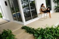 Woman sitting on patio, reading magazine - Alex Mares-Manton
