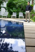 Man standing by swimming pool, hands in pocket - Alex Mares-Manton