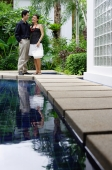 Couple standing side by side next to swimming pool - Alex Mares-Manton