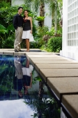 Couple standing by swimming pool, smiling at camera - Alex Mares-Manton