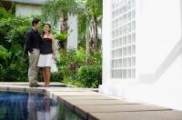 Couple standing next to swimming pool - Alex Mares-Manton