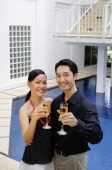 Couple by poolside, holding up champagne glasses towards camera - Alex Mares-Manton