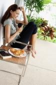 Woman having coffee on patio, hand on head - Alex Mares-Manton
