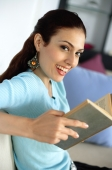 Woman holding book, smiling at camera - Alex Mares-Manton
