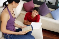 Couple in living room, man lying on sofa with laptop, woman holding book - Alex Mares-Manton