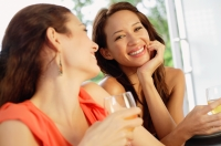 Two women with wine glasses, one smiling at camera - Alex Mares-Manton