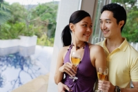 Couple holding wine glasses, looking at each other - Alex Mares-Manton