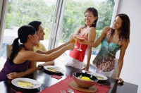 Young adults in dining room toasting with wine glasses - Alex Mares-Manton