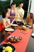 Young adults having dinner party, toasting with wine glasses - Alex Mares-Manton
