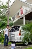 Man washing car, woman standing on balcony looking down - Alex Mares-Manton