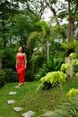 Woman in red outfit, walking through garden - Alex Mares-Manton