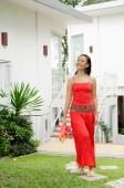 Woman holding flowers, walking through garden - Alex Mares-Manton