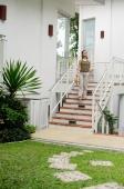 Woman walking down stairs to garden - Alex Mares-Manton