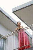 Woman standing on balcony, leaning on railing - Alex Mares-Manton